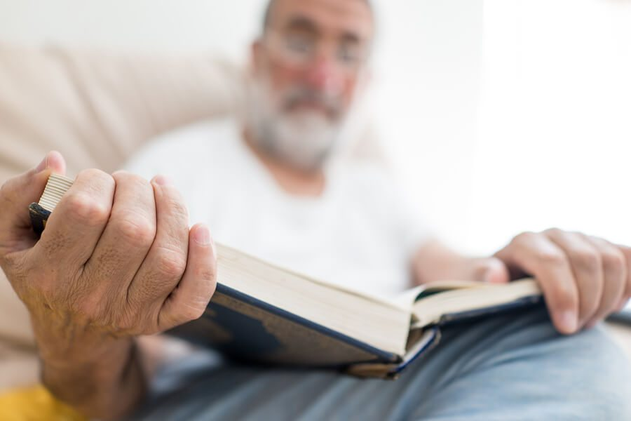 Elderly man sitting and reading a book